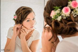 Braut beim Getting Ready guckt in Spiegel und legt sich Schmuck an