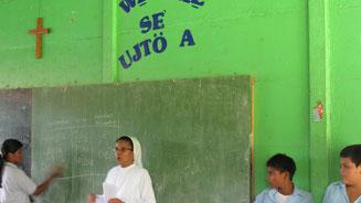 Szene in einem Klassenraum, an der Wand siehst du ein paar Wörter in der Sprache der Bribri