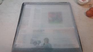 Auf Backblech ein Blatt Zeitungspapier und darauf das Backpapier legen