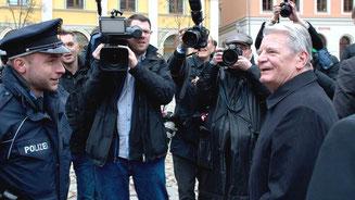 Bundespräsident Joachim Gauck unterhält sich bei seinem Besuch in Bautzen mit einem Polizisten. © Arno Burgi/dpa