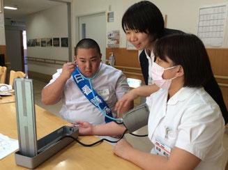 (血圧測定を実際に菅原師長と共に行っている様子)