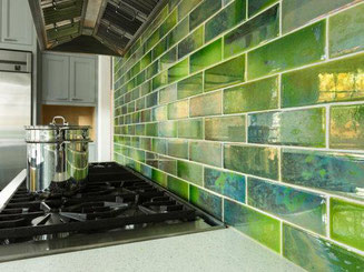Close up of a kitchen backsplash with lime green glazed tiles. The kitchen countertop is white quartz and there's a stainless steel pot on the stovetop.