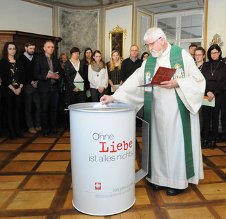"""Caritas-Direktor Franz Mattes übergibt einen Umschlag mit einem """"Herzenswunsch"""" an die Caritas-Spendendose. (Foto: Peter Esser)"""