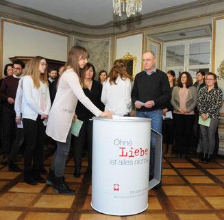 """Mitarbeiterinnen und Mitarbeiter der Caritas übergeben ihre Umschläge mit """"Herzenswünschen"""" der Caritas-Spendendose. (Foto: Peter Esser)"""
