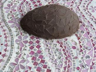 Mosaik-Schoko-Osterei auf rosa Verpackung gebettet