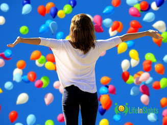 woman with arms outstretched feeling confident with balloons and blue sky