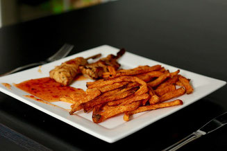 Teller mit Fleischstücken und Pommes