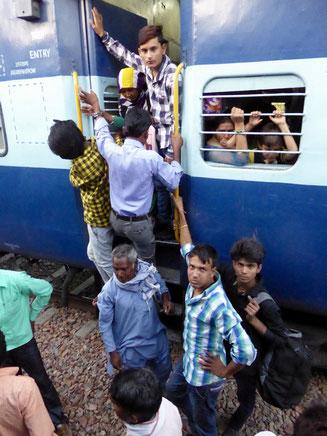 Bild: Menschen in Indien steigen in einen Zug
