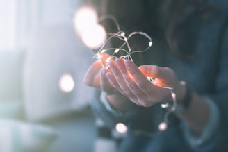 女性がぼんやり輝くオーナメントライトを両手に持つ画像