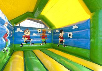 Kinder spielen Fußball in der Hüpfburg