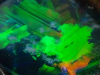 Das Farbenspiel des Edelopals enteht durch winzig kleinen Kugeln aus amorpher Kieselsäure, die das Licht beugen und reflektieren, sogenanntes Opalisieren. Die grösseren Kügelchen geben das rote Feuer, die kleinen das Grün bis Violett.