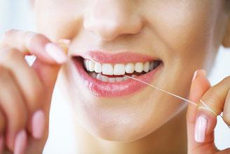 Strahlend weiße Zähne mit der Zahnseide nach dem Zähneputzen