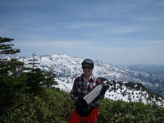 釈迦岳山頂。転がっていた道標を抱えてやたら嬉しそう。背景は別山。