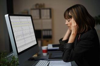 Frau vor dem PC mit Kopfschmerzen