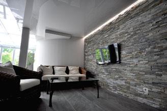 Bild Wohnraum mit Steinwand, Lichtkanal-Technik und weißer Lackspanndecke (deckenpartner GmbH).