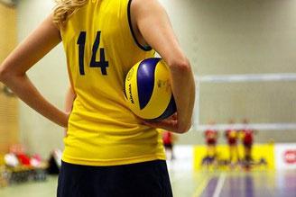 Handballspielerin mit Ball schaut auf ihr Team