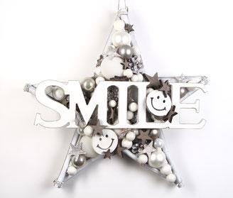 Weiße Wand Deko mit SMILE Schild aus Holz und lustigen Smileys.