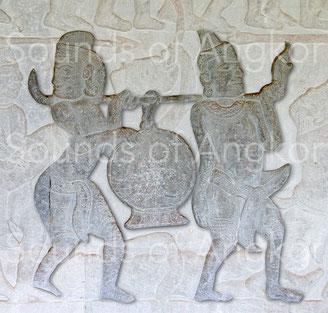 Tambour sur portant avec support. Le porteur postérieur ne tient pas de bâton. Le batteur a peut-être été tué. Un homme gît à terre sous le tambour. Angkor Vat, Galerie nord. Victoire de Krishna sur l'Asura Bāna. XVIe s.