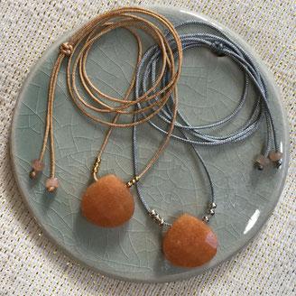 Goutte en pierre de gemme (quartz rose, quartz fumé ou crystal) entourée de perles dorées monté en collier pour femme sur fil de jade réglable à l'aide d'un noeud coulissant.
