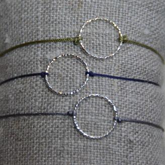 Un anneau en argent 925 diamanté monté sur un fil de jade réglable.