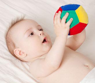 Baby liegt nur mit Windel bekleidet auf dem Rücken. Baby betrachtet einen Ball, den es in der Händen hält.