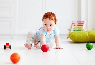 Bébé jouant au sol avec des balles, favorisant l'intégration des réflexes archaïques par le mouvement naturel