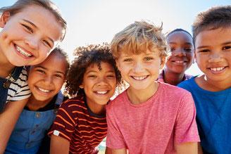 Groupe d'enfants tous souriants, ayant des réflexes archaïques bien intégrés qui leur permettent d'accéder à tout leur potentiel d'apprentissage, à une gestion sereine de leurs émotions et n'ayant pas de troubles de posture