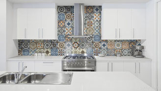 Kitchen with white cabinets and countertops and a patterned, colorful tile backsplash