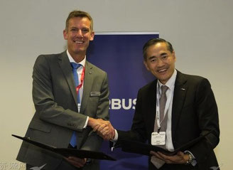 SingPost's Mervin Lim (right) confirms deal with Airbus Helicopters' Jean-Brice Dumont