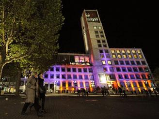 Menschen laufen am Abend während der Stuttgartnacht vor dem beleuchteten Rathaus. Foto: Marijan Murat