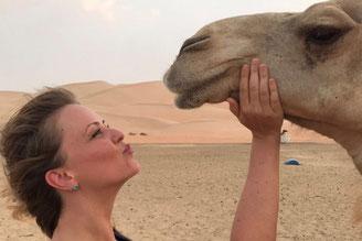 Nicole im Profil, die Hände am Kinn eines Kamels, das ihr gegenüber steht