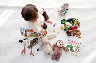 Baby spielt auf Decke mit Spielzeug
