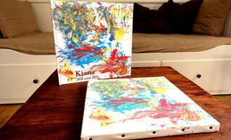 Kleine Künstler Kinderkunstbuch und mit Fingerfarben bemalte Leinwand auf dem Couchtisch
