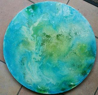 Een rond schilderij met de oceaan van boven gezien in bleuwe en groene zee tinten als bovenkant van een oceandrum, gemaakt door Joke Zonneveld
