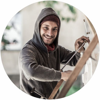 Marcus Scheffczyk blickt von seiner Arbeit am Punktiergerät lächelnd in die Kamera