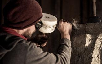 Steinmetz Marcus Scheffczyk bearbeitet Sandstein mit einem Zahneisen