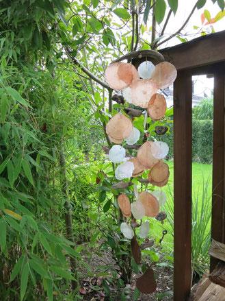 Klangspiel mit Treibholz und Capiz vor Bambus aufgehängt.