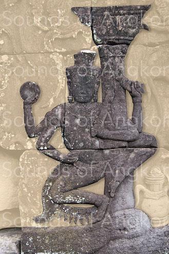3a. Viṣṇu tenant une conque dextrogyre. L'apex fermé ne permet pas de voir le sens de l'enroulement. En revanche la columelle continue à la base du pouce, confirmant le sens de l'enroulement. Bayon.