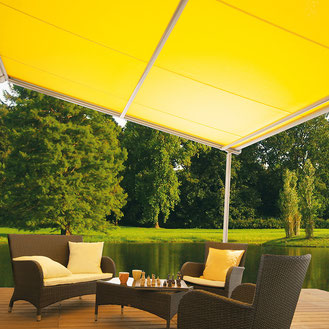 Gelbe Pergolamarkise über einer Terrasse mit brauner Sitzgarnitur vor einem See