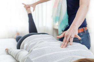 Femme réalisant une pression au niveau du dos d'un patient lors de l'intégration des réflexes archaïques selon l'approche d'Intégration Motrice Primordiale