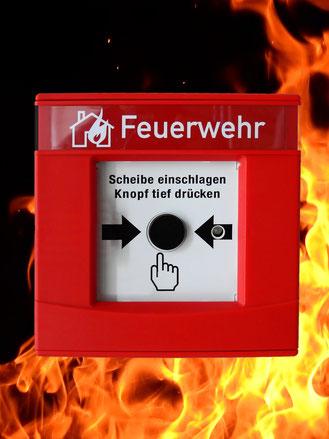"""Roter Handalarmtaster mit der Aufschrift """"Feuerwehr""""; als Hintergrund gelb-rote Flammen"""