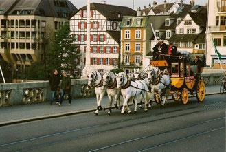 Postkutsche gezogen von 5 Schimmeln auf der mittleren Brücke in Basel