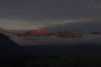 Die untergehende Sonne bringt die Alpen zum Glühen