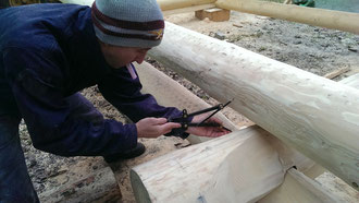 Naturstammhaus - Baustelle - Zimmermann bei der Arbeit - Profil und Eckverkämmungen werden auf der Baustelle eingearbeitet