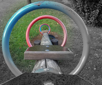 Blick durch die Festhalteringe einer Spielplatzwippe