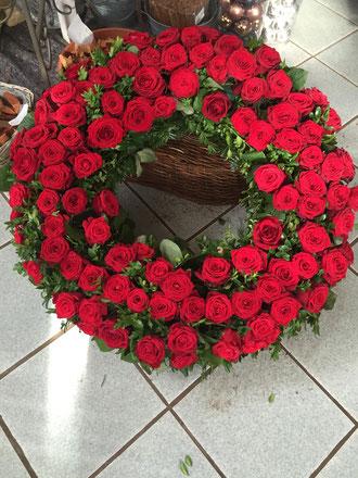 Rundgesteckter Kranz mit roten Rosen