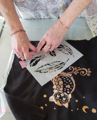Photo d'atelier, mains qui posent un pochoir représentant des plumes  sur du tissu noir , la peinture est dorée et argentée