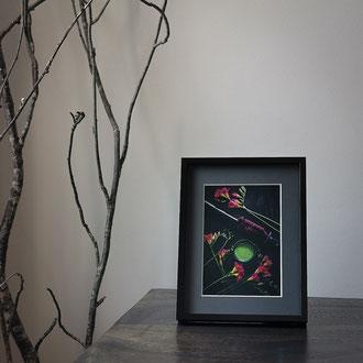 Kunstdruck einer gerahmten Fotografie zeigt eine dunkle Teeschale mit Matcha und ein Schwert