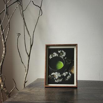 Kunstdruck einer gerahmten Fotografie zeigt eine dunkle Teeschale mit Matcha und weißen Kirschblueten