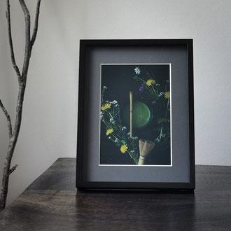 Kunstdruck einer gerahmten Fotografie zeigt eine Teeschale mit Matcha im fruehlingshaften Blumenarrangement